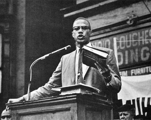 Malcolm X discursando com alcorão
