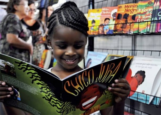Criança negra lendo livro